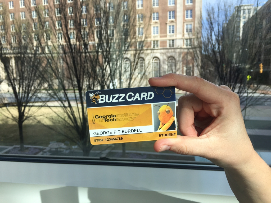 BuzzCard Held in Hand, in front of trees and Midtown Atlanta building